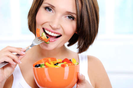 Portrait of a beautiful caucasian smiling young woman eats vegetable salad photo