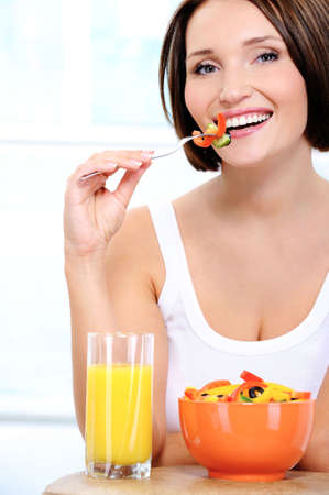 The beautiful cheerful young woman has breakfast salad from fresh vegetables with orange juice  photo