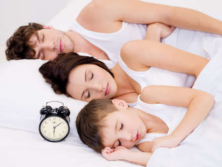 Three person of the young family sleeping with alarm clock near  their  heads photo