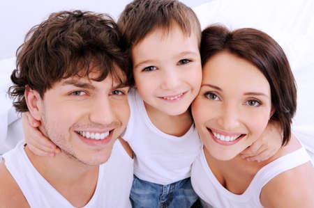 familia abrazo: De personas se enfrenta a una sonrisa hermosa. Una familia feliz de j�venes de tres personas