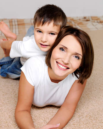Beautiful young mother with  the lovely smiling son lying at it on a back