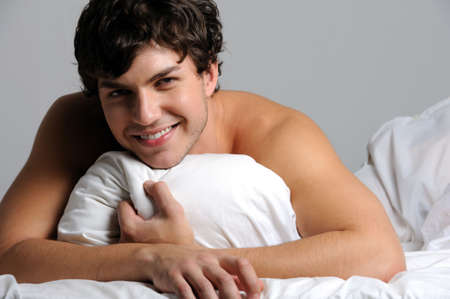Portrait of a beautiful smiling young man lying in bed with pillow photo