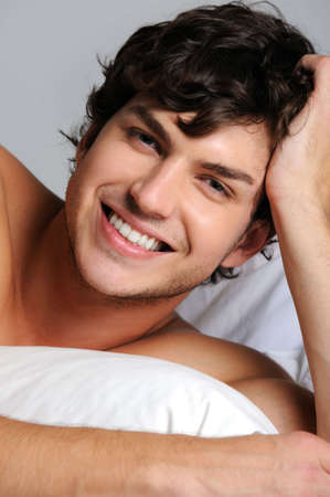 Closeup face of a smiling happy young man lying in bed photo