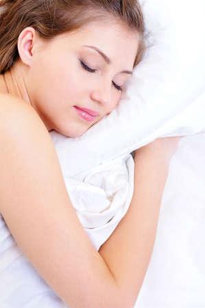 Young cute fresh woman dreaming embracing white pillow photo