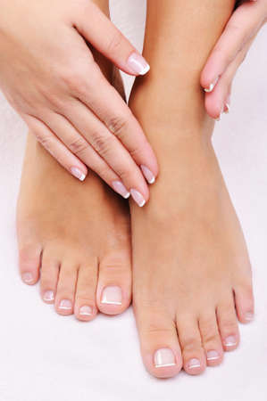 Beautiful care female feet with the hand with a French manicure  photo