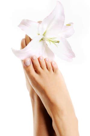 pedicura: Hermosas pies mujeres saludables con flores de lirio sobre un fondo blanco