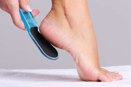 woman scrubbing  heel in beauty salon use the   tool for pedicure photo