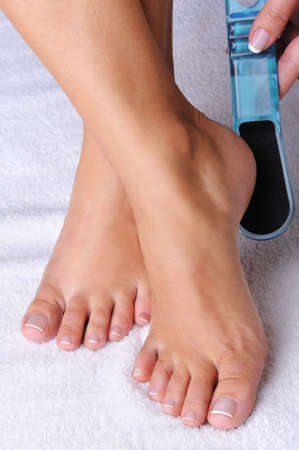 female feet: Young woman scrubbing her feet uses the cleaning   brush for a pedicure Stock Photo