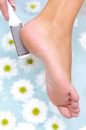 sole: female scrub and clean the well-groomed foot in water by means of a clearing steel  brush