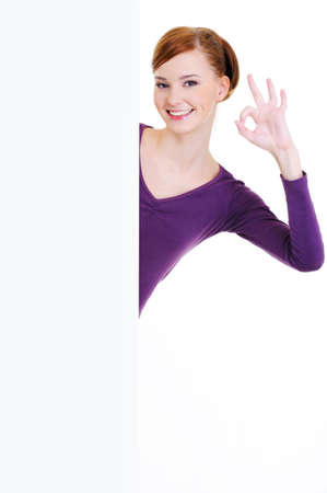 The young beautiful smiling woman looks out because of a blank white advertising banner with okay gesture Stock Photo - 6653074