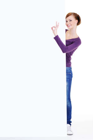 Full-length portrait of a young woman looks out because of  advertising billboard with okay gesture