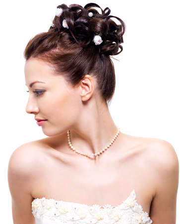 Profile portrait of a beautiful bride with wedding hairstyle - on white background photo