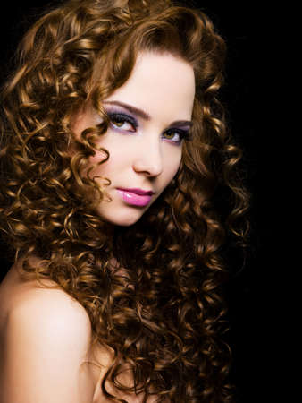 curly hair model: Attractive young  woman with  long ringlet hairs - isolated on black