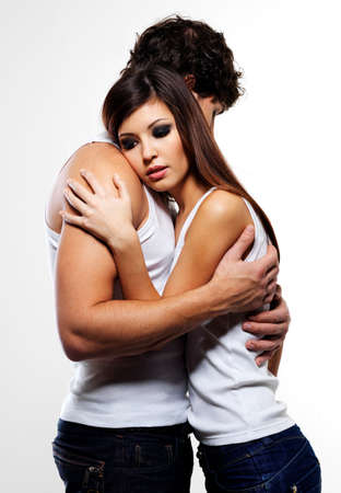Two young beautiful embracing lovers - posing at studio  photo