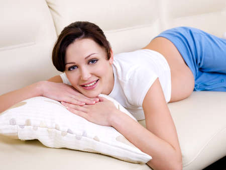 Beautiful cheerful pregnant woman lying on the sofa Stock Photo - 6657114