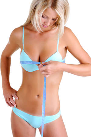 young breast: Beautiful young woman in underwear with a slender health body  measures breast. Front view over white background.