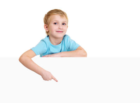 Cute blond little boy is above on a white banner and points on it. photo