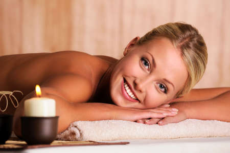 Close-up portrait of a beautiful smiling female lying down in beauty salon photo