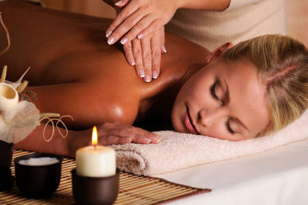 back massage: professional masseur doing  massaging  female neck  in the beauty salon