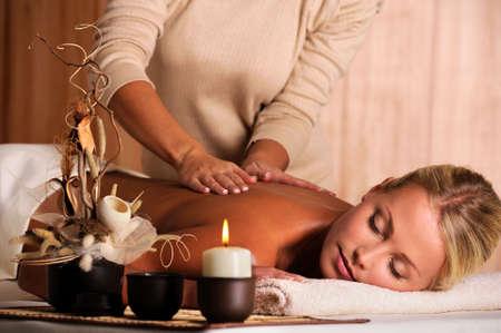 masaje corporal: masajista profesional haciendo masajear detr�s de una hermosa mujer joven