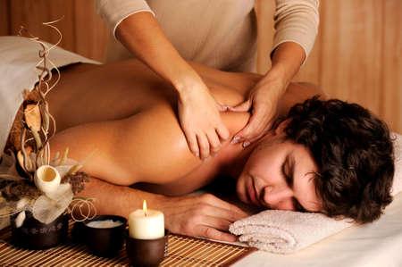 massage hands: Handsome man getting massage in the beauty salon - low key light
