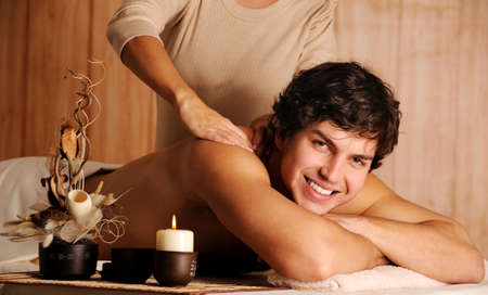 Beautiful male getting relaxation massage in spa salon photo
