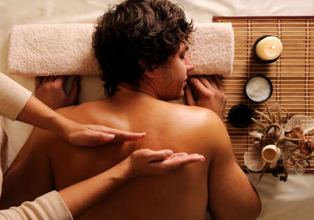 man lying down: The masseur does back massage to the young guy in a beauty salon