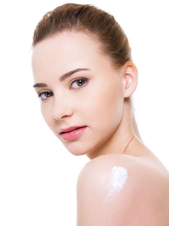 Beauty caucasian young woman with cosmetic cream on shoulder - isolated on white photo