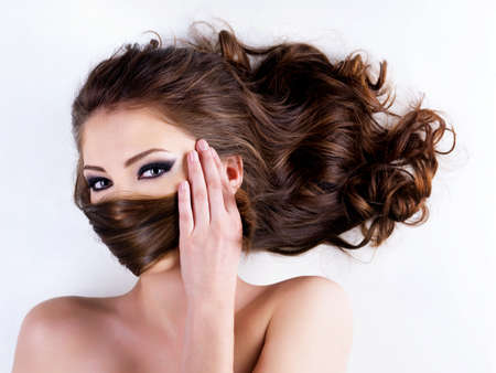 Close-up portrait of a beautiful woman covers the face by long brown  hairs Stock Photo - 6750482