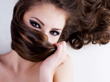Close-up portrait of a beautiful woman with beauty black eyes and long brown hairs photo