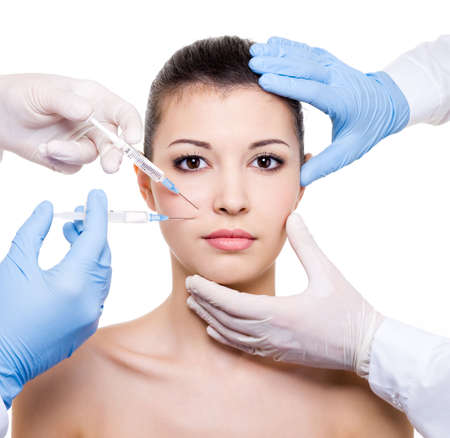 botox: Plastic surgeons giving injection of botox in female lips - isolated white