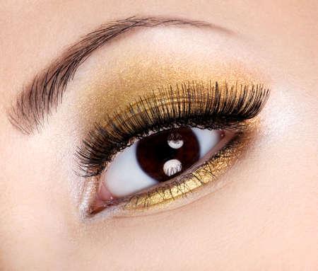 mascara: Eye make-up with bright fashion golden eyeshadow  Stock Photo