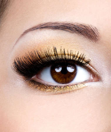 Fashion eye make-up with golden eyeshadow - macro shoot photo