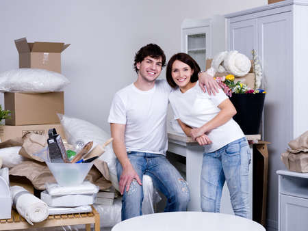 Happy cheerful young couple embracing in the new flat - indoors photo