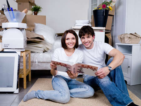Happy couple sitting on the floor together with the photo album photo