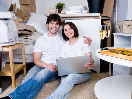 Happy couple sitting on the floor with laptop after moving photo