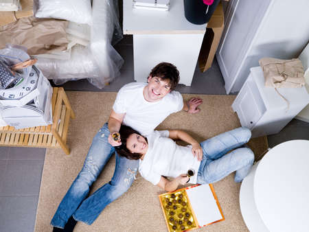 Smiling happy young couple lying on the floor and celebrating new home - high angle photo