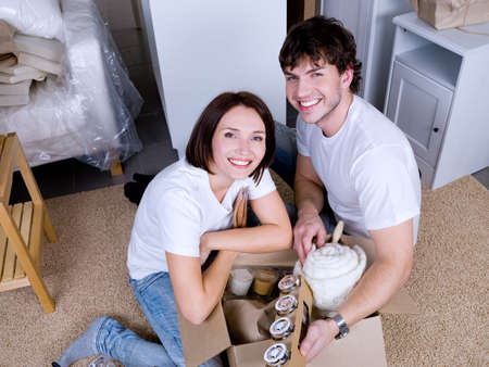 to unpack: happy young couple unpacking their things after moving