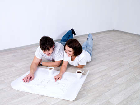 Young couple lying on the floor and looking at the plan of room photo