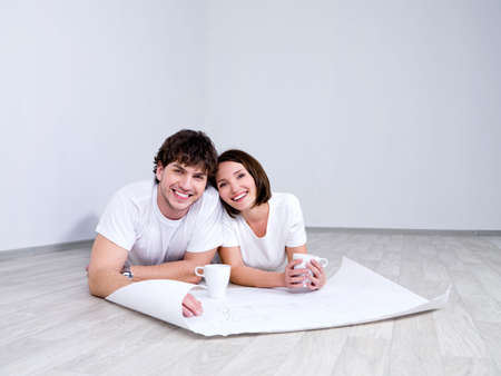 unfurnished: Young couple lying on the floor with plan of new room