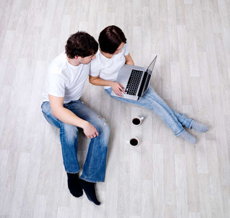 Couple sitting on the floor with laptop in the empty room - High angle view photo