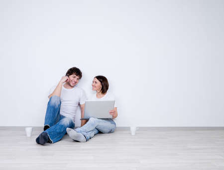 pareja en casa: Hermosa pareja sonriente relajarse en la sala vac�a con el port�til - nueva casa