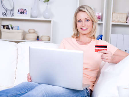 Beautiful smiling young woman with laptop holding credit card  photo