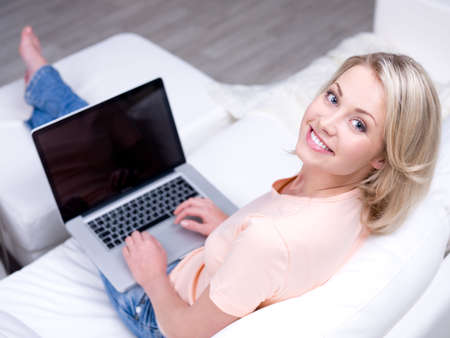 attractive couch: Smiling happy woman sitting on the sofa and using laptop - High angle view