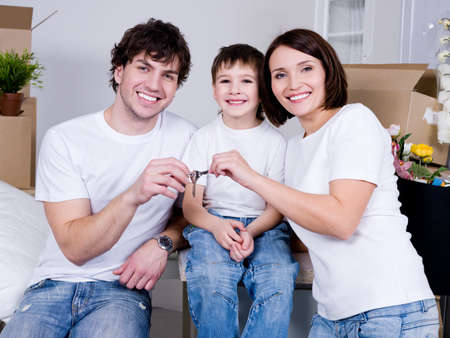 Happy young family sitting in their new flat - indoors photo