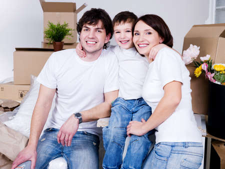 Young happy friendly family sitting together in their new flat photo