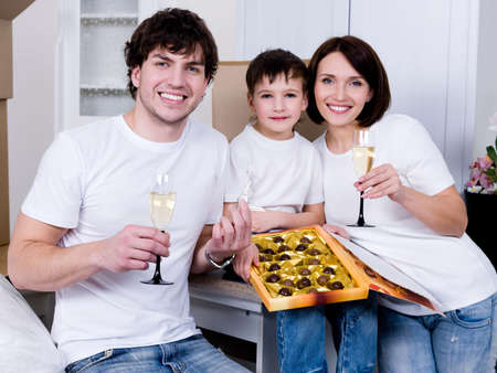 Happy young family celebrating new home together - indoors photo