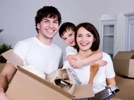 home moving: Happy young friendly family in their new flat - indoors