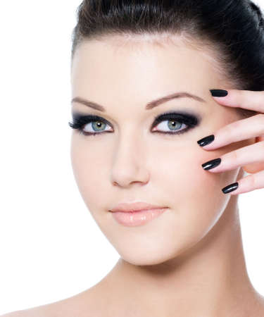 eyeshadows: portrait of a young beautiful woman with fashion black make-up and manicure - isolated on white
