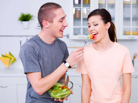 vegetables young couple: Happy young couple eating salad in the kitchen Stock Photo